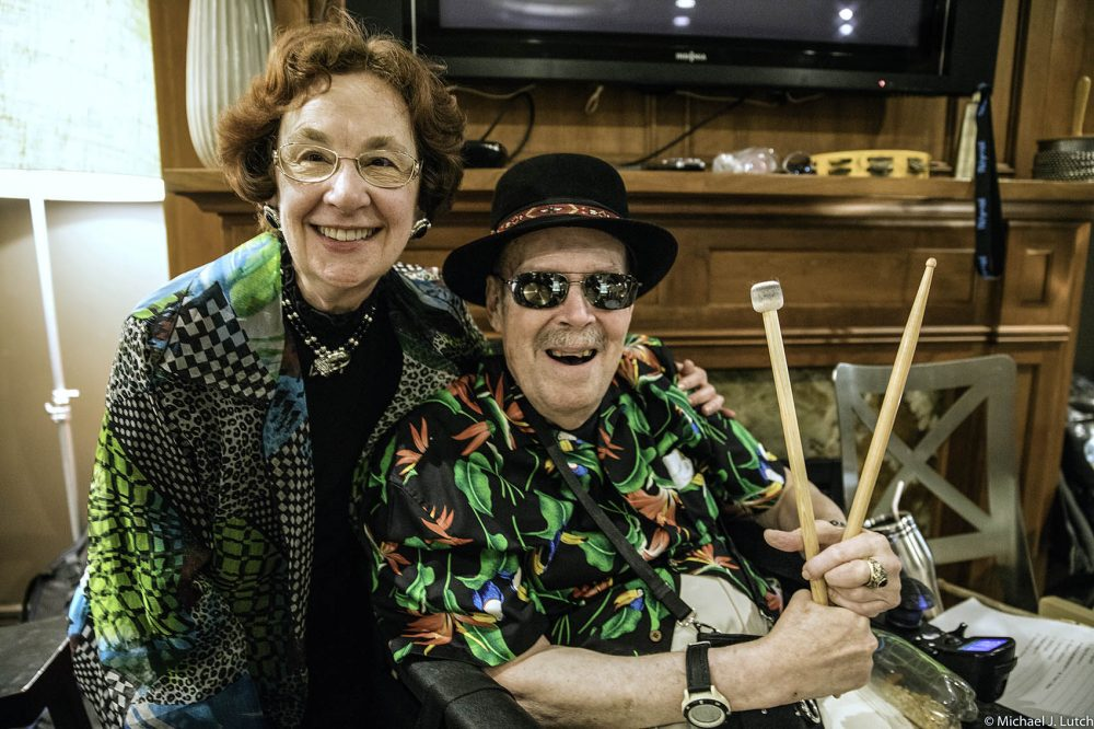 Tony Swartz-Lloyd, 79, started learning how to play the drums at 74. He'd been living with Parkinson's disease for 12 years and sought out a drumming group at Beth Israel Deaconess Medical Center for people with the disease. Here, he poses for a photo with his wife, Marilyn. (Courtesy Michael J. Lutch)