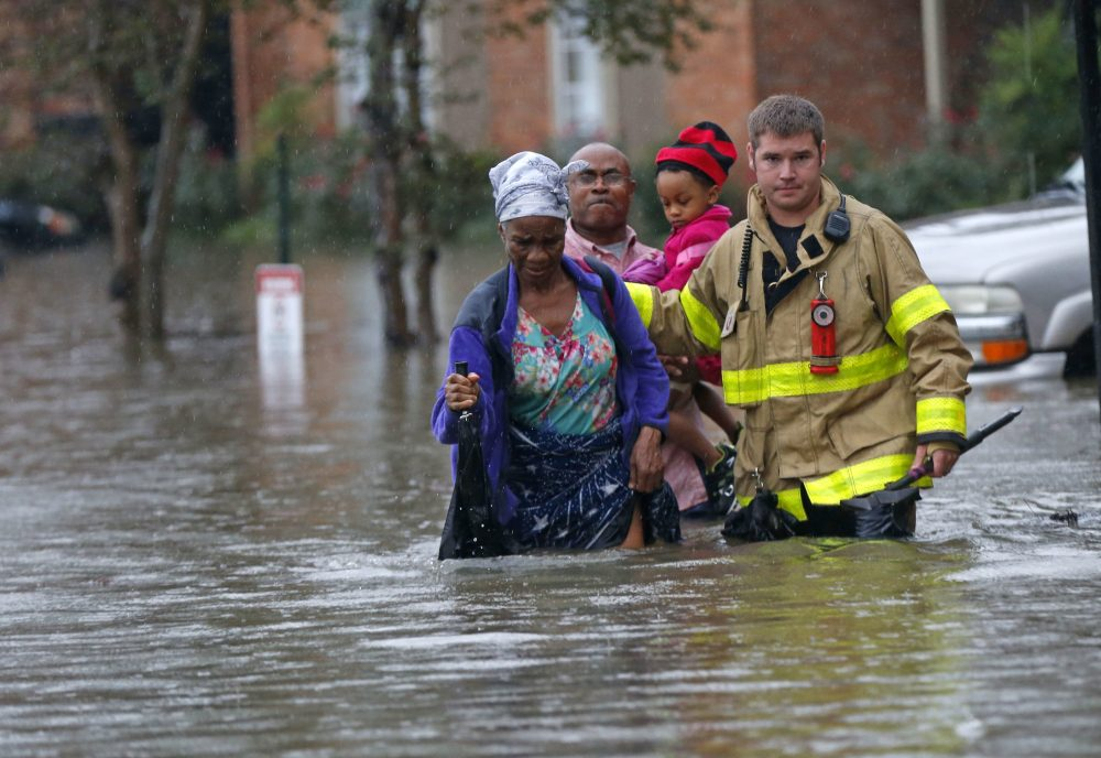 A member of the St. George Fire Department assists residents as they wade through floodwaters from heavy rains in Baton Rouge, Louisiana on Friday, Aug. 12, 2016. (Gerald Herbert/AP)