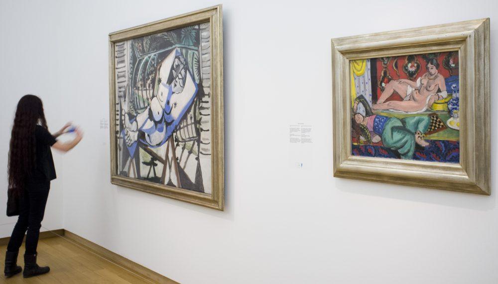 "A woman takes a pictures of a painting titled ""Two Odalisques, One Undressed, Ornamental Background and Checkerboard"" dated 1928 by French artists Henri Matisse (1869-1954), right, next to a painting by Pablo Picasso titled ""Nude in front of a Garden,"" left,  during a press preview of the exhibit ""The Oasis of Matisse"" at Stedelijk Museum in Amsterdam, Netherlands in 2015. (Peter Dejong/AP)"