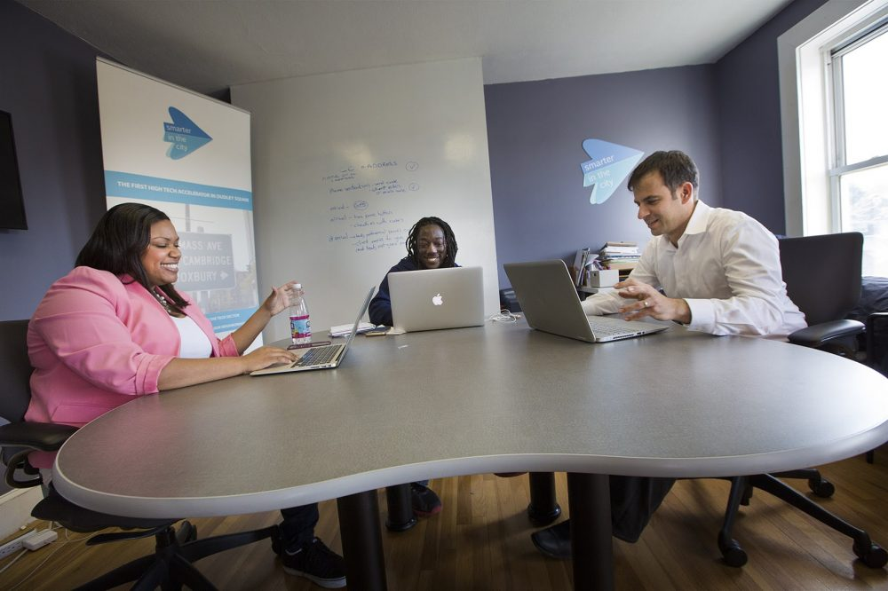 Melissa James, Kofi Callender and Gilad Rozensweig, founder of Smarter in the City, talk in a conference room at the accelerator's Roxbury location. (Jesse Costa/WBUR)
