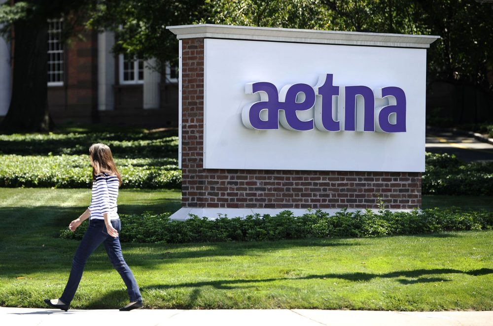 In this Tuesday, Aug. 19, 2014, file photo, a pedestrian walks past a sign for health insurer Aetna Inc., at the company headquarters in Hartford, Connecticut. (Jessica Hill/AP)