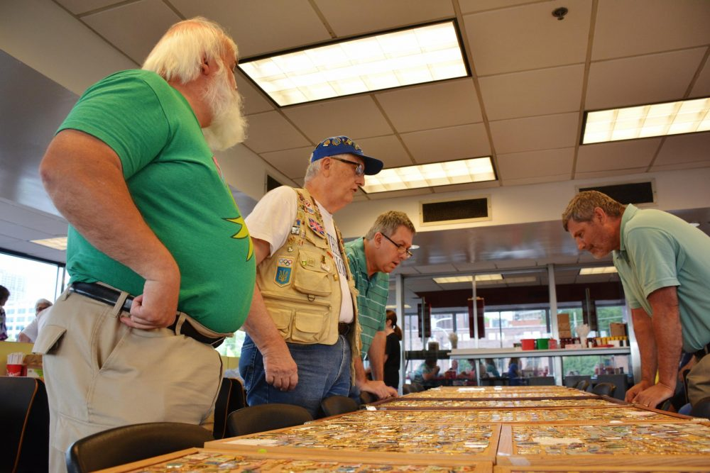 Randy Parsons (front) speaks with other Olympic pin traders at the monthly pin show in Atlanta. The event has been happening at the Varsity drive-in since the 1996 Olympics. (Sam Whitehead/GPB)