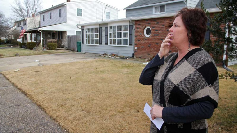 Debbie Fleming, holding a list of nine recovery homes in her neighborhood in Levittown, Pennsylvania, pauses outside a recovery home on Goldengate Road. (Emma Lee/WHYY)