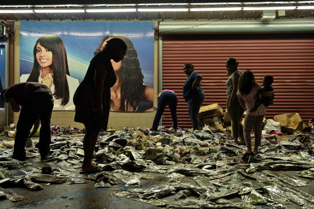 People sort through water damaged products outside Jasmine's Beauty Supply following the floods on Aug. 16, 2016 in Baton Rouge, Louisiana. (Brendan Smialowski/AFP/Getty Images)