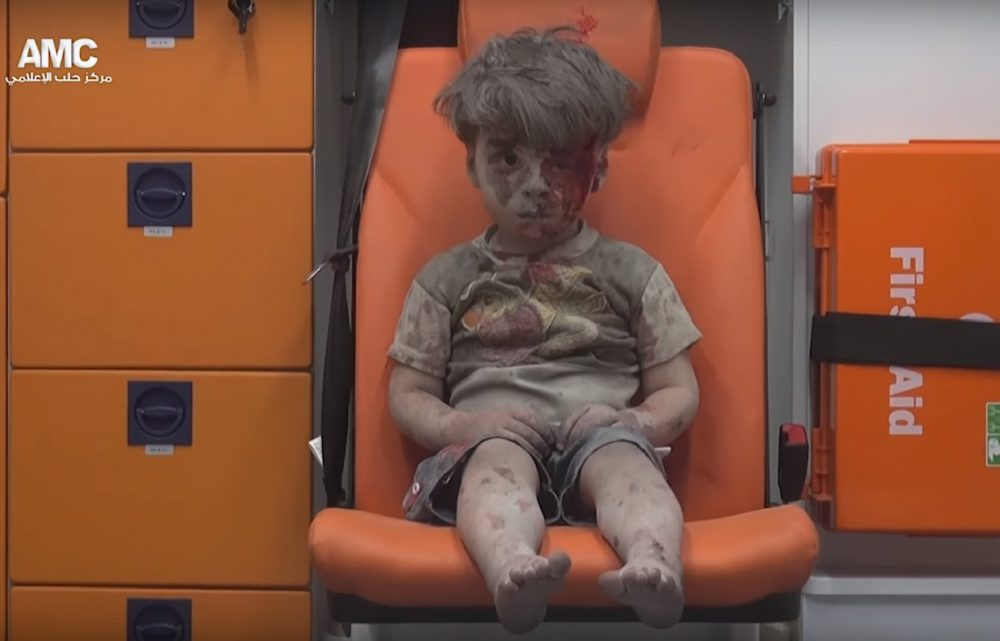 A 5-year-old boy, identified in news reports as Omran Daqneesh, sits in an ambulance Wednesday after an airstrike in Aleppo, Syria. (Aleppo Media Center)
