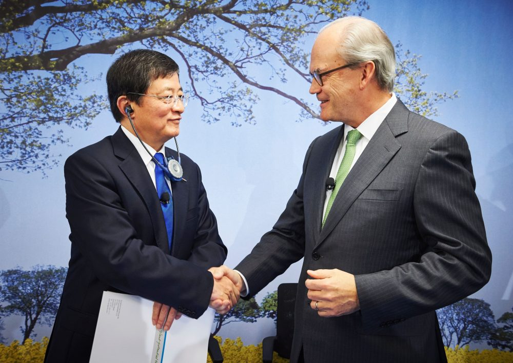 Chairman of Swiss farm chemicals giant Syngenta, Michel Demare shakes hands with Chairman of ChemChina Ren Jianxin during a press conference on Feb. 3, 2016. (Michael Buholzer/AFP/Getty Images)