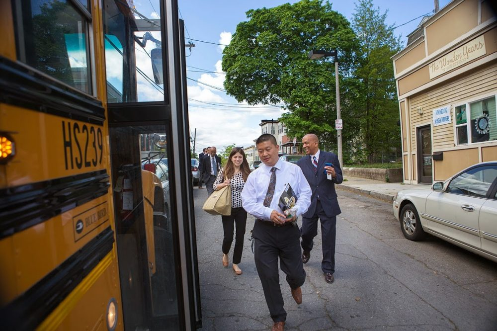 Boston Public Schools Superintendent Tommy Chang, center, walks toward a school bus in May 2015. (Jesse Costa/WBUR file photo)