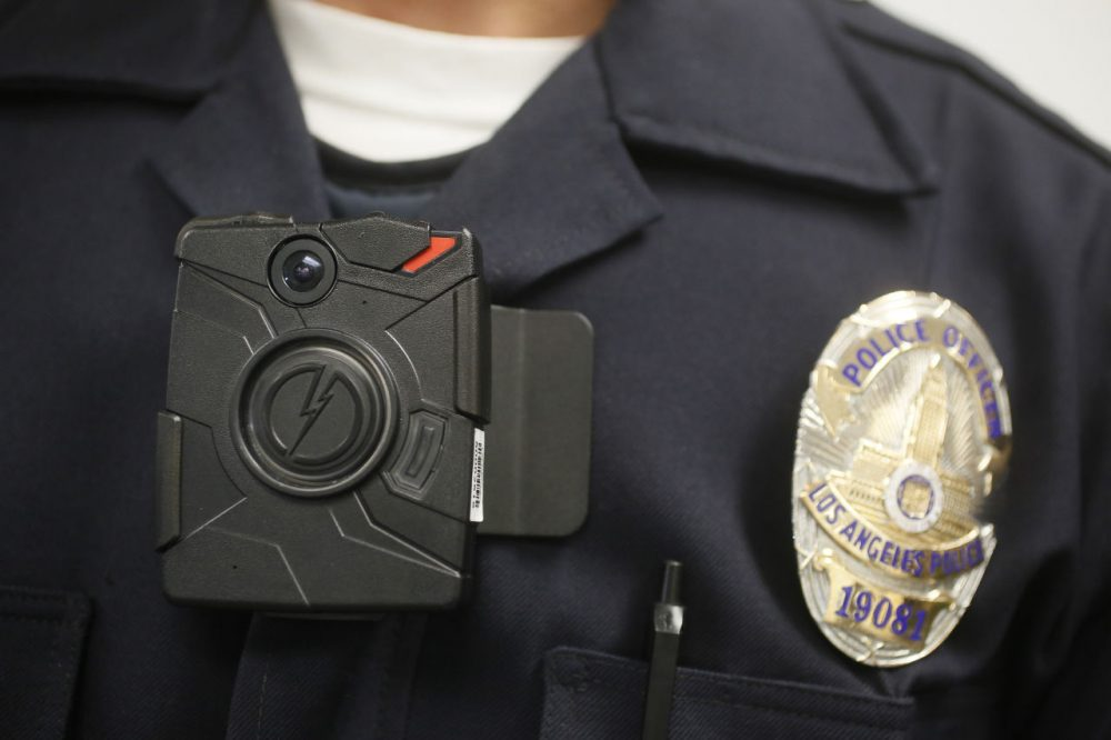 A Los Angeles Police officer wears an on-body camera during a demonstration for media in Los Angeles in 2014.  100 Boston police officers have begun a six-month body camera pilot program. (Damian Dovarganes/AP)