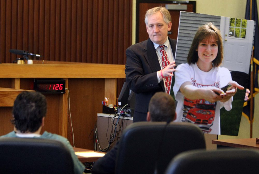 """Bob Marriott holds a large photo of his daughter Elizabeth """"Lizzy"""" Marriott as he looks at Seth Mazzaglia, seated left, during a sentencing hearing in Strafford County Superior Court, Thursday, Aug. 14, 2014, in Dover, N.H. Mazzaglia was convicted of killing Elizabeth Marriott and was sentenced to life in prison. (Jim Cole/AP)"""