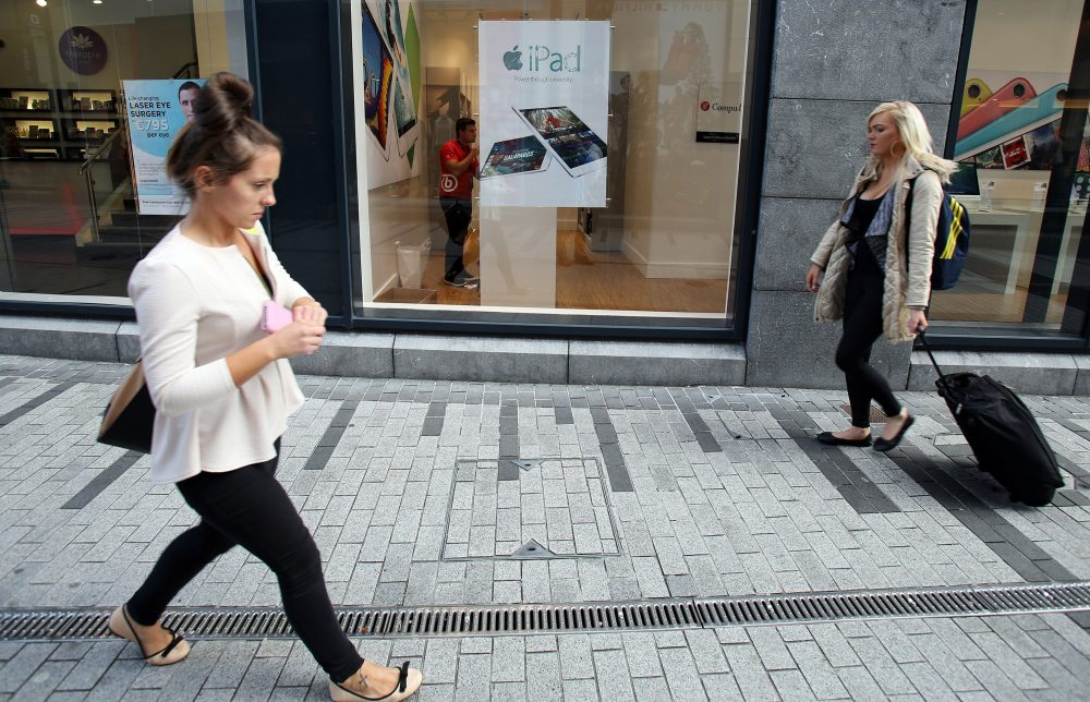 People walk past a computer shop selling Apple products in Cork, Ireland on Oct. 2, 2014. (Paul Faith/AFP/Getty Images)