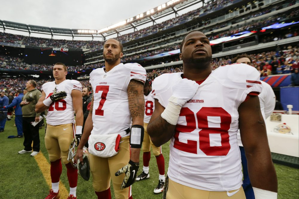 San Francisco 49ers quarterback Colin Kaepernick (7) stands with teammates during the playing of the national anthem before a 2014 NFL football game. (Julio Cortez/AP)