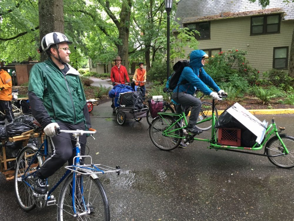 Volunteers move the belongings of Nate Martin, a graduate of Reed College, by bike to an apartment in northeast Oregon ten miles away. (Jill Ryan/Here & Now)