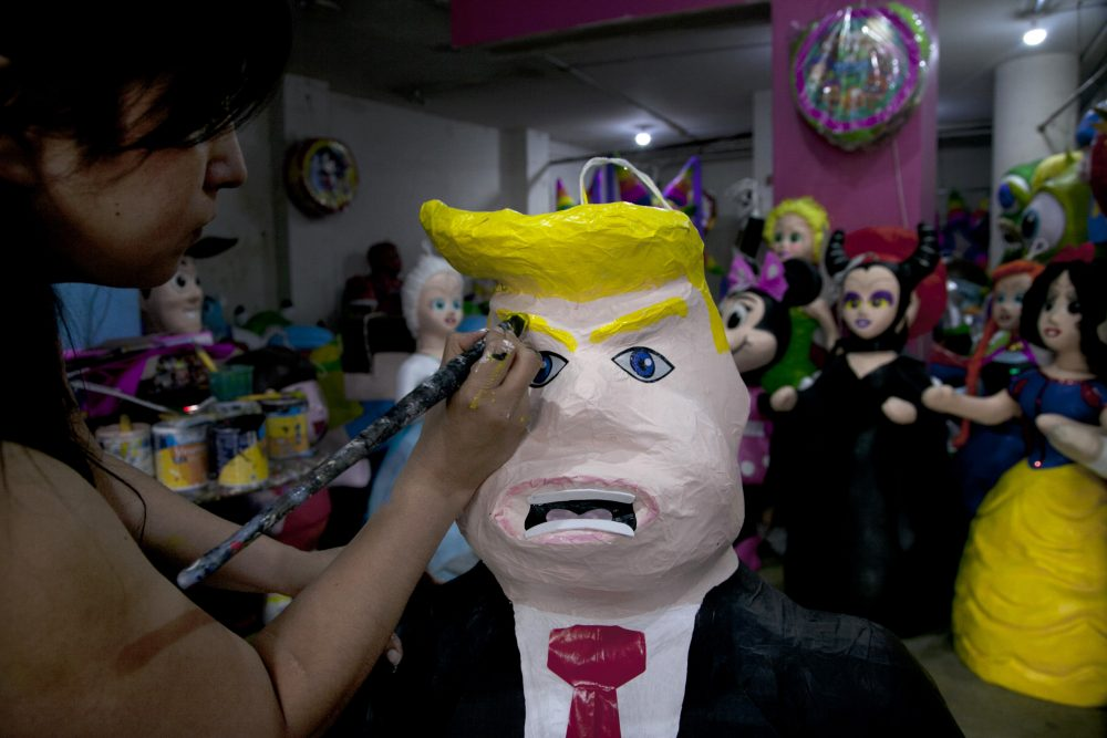 """Alicia Lopez Fernandez paints a pinata depicting Donald Trump at her family's store """"Pinatas Mena Banbolinos"""" in Mexico City. In a surprise move, Donald Trump will travel to Mexico on Wednesday, Aug. 31, to meet with President Enrique Pena Nieto, just hours before the Republican delivers a highly anticipated speech on immigration. (Marco Ugarte/AP)"""