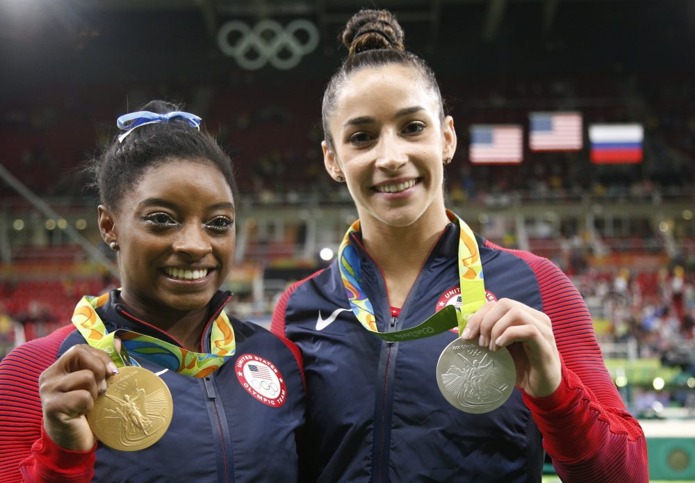 Aly Raisman (right) stands with teammate Simone Biles (left) after they won the silver and gold medals, respectively, for the women's gymnastics individual all-around at the 2016 Summer Olympics in Rio. (Dmitri Lovetsky/AP)