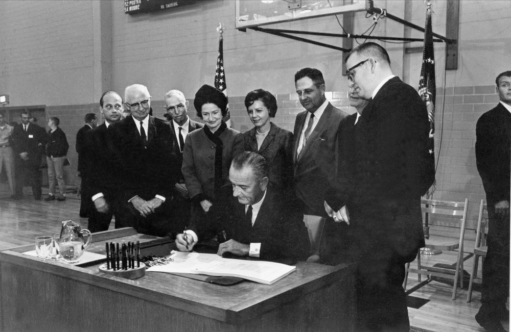 "U.S. President Lyndon B. Johnson, seated at the desk he used while a student secretary at Southwest Texas State College 35 years ago, signs the Higher Education Act at San Marcos, Texas, Nov. 8, 1965.  Looking over the president's shoulder is Lady Bird Johnson and to her right are Mrs. Jake Pickle; Rep. James Jarrell ""Jake"" Pickle, D-Texas; J.C. Kellam, of Austin, partially hidden; and James H. McCrocklin, president of the college.  The men at extreme left are not identified.  (AP Photo)"