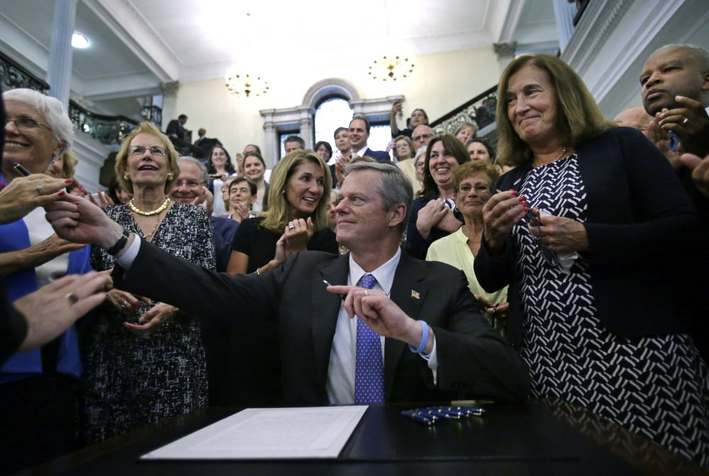 Gov. Charlie Baker hands out pens to supporters, including state Treasurer Deborah Goldberg, right, after signing a bill into law at the State House Monday that requires men and women be paid equally for comparable work in Massachusetts. (Elise Amendola/AP)