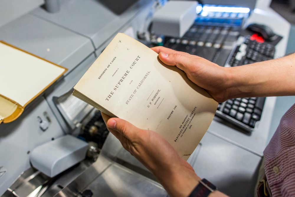 Harvard's Library Innovation Lab is working to digitize nearly 40 million pages of case law from the Harvard Law School library collection, so the public can access it online and for free. Here, a case law book that has been cut from its binding is ready to go through a high speed scanner. (Brooks Kraft/Harvard Law School)