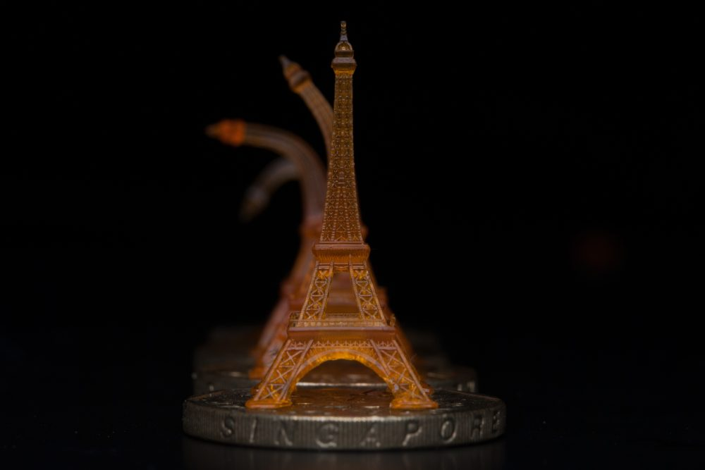 A shape memory Eiffel tower was 3-D printed using projection microstereolithography. Here you can see it recovering from being bent after toughening on a heated Singapore dollar coin. (Courtesy of Qi (Kevin) Ge/MIT)