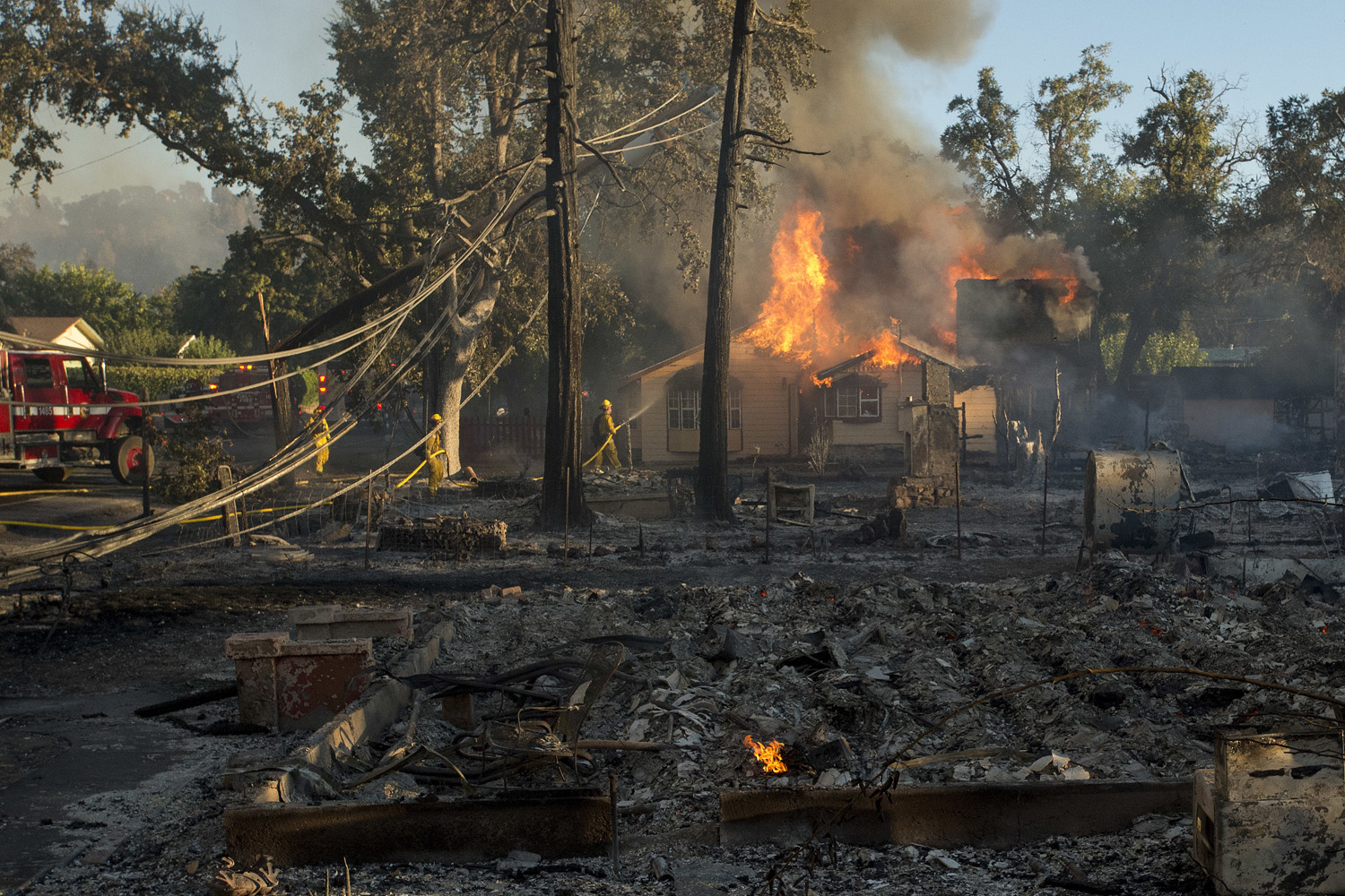 Firefighters douse a burning house in the town of Lower Lake, Calif., on Sunday, Aug. 14, 2016. (Josh Edelson/AP)