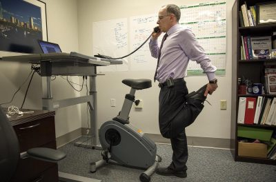 Dr. Eddie Phillips stretches as he talks on the phone at his office at the VA Boston Healthcare System. (Robin Lubbock/WBUR)