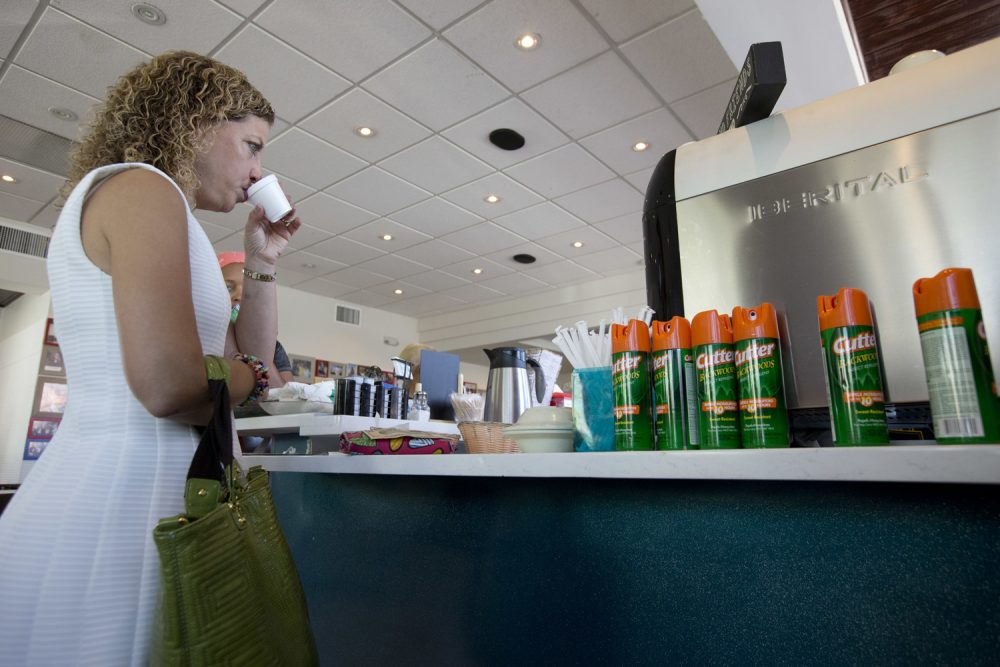 U.S. Rep. Debbie Wasserman Schultz, sips Cuban coffee next to a counter with cans of insect repellent after holding a news conference at David's Cafe Cafecito, Monday, Aug. 22, 2016, in Miami Beach, Fla. (Wilfredo Lee/AP)