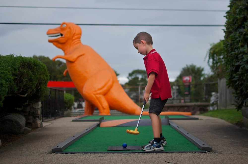 After more than 50 years, the old-fashioned miniature golf course off Route 1 in Saugus is closing. The spot is well known for its DayGlo orange T-rex that, from the sixth hole, gazes over the highway. Here, Louie Schraffa, 5, of East Boston, prepares for a putt on the dinosaur hole, Sept. 29, 2015. (Sharon Brody/WBUR)