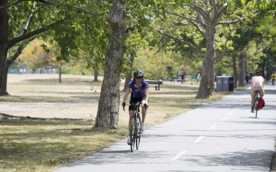 A woman rides a bike along the Esplanade. (Joe Difazio for WBUR)