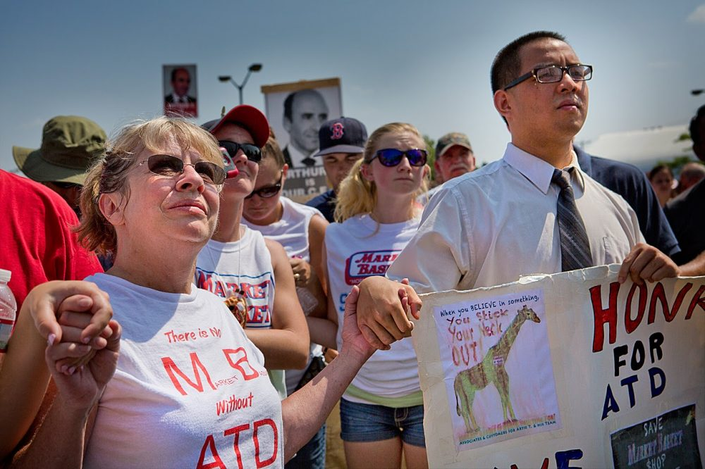 Protesters hold hands in solidarity as they rally in support of ousted Market Basket CEO Arthur T. Demoulas in Tewksbury on August 5, 2014. (Jesse Costa/WBUR)
