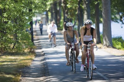 Cyclists ride their bikes along the Charles River by Storrow Drive in Boston. (Jesse Costa/WBUR)
