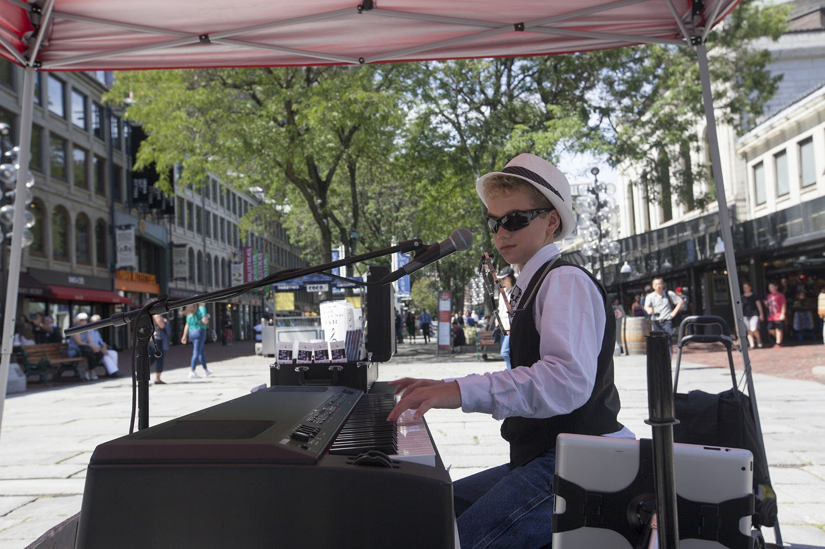 Bradley Bartlett-Roche, known as the Boston Piano Kid, plays in Faneuil Hall this summer. (Joe Difazio for WBUR)