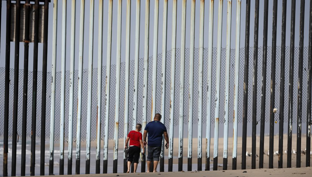 Two people walk towards metal bars marking the United States border where it meets the Pacific Ocean Wednesday, March 2, 2016, in Tijuana, Mexico. (Gregory Bull/AP)