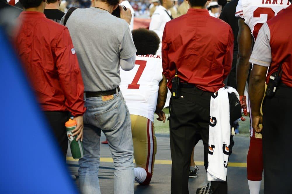 San Francisco 49ers quarterback Colin Kaepernick, middle, kneels during the national anthem on Thursday night. (Denis Poroy/AP)