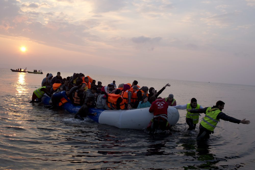 Volunteers help migrants and refugees on a dingy as they arrive at the shore of the northeastern Greek island of Lesbos, after crossing the Aegean sea from Turkey. (Petros Giannakouris/AP)