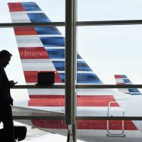 In this Jan. 25, 2016 file photo, a passenger talks on the phone as American Airlines jets sit parked at their gates at Washington's Ronald Reagan National Airport. (Susan Walsh/AP)