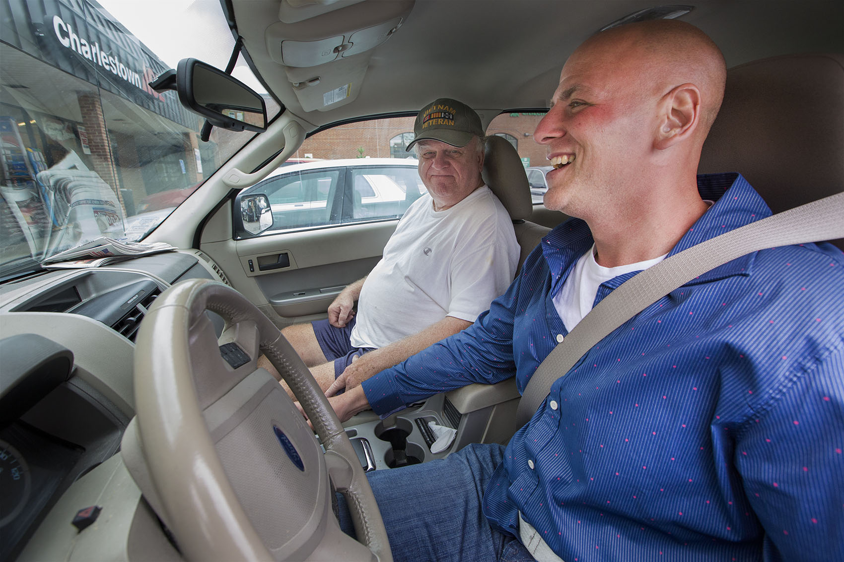 In the parking lot of the Bunker Hill Shopping Mall, Joe Donovan gets a driving lesson from his father, Joe Sr. Joe had never gotten his license before he was incarcerated. (Jesse Costa/WBUR)