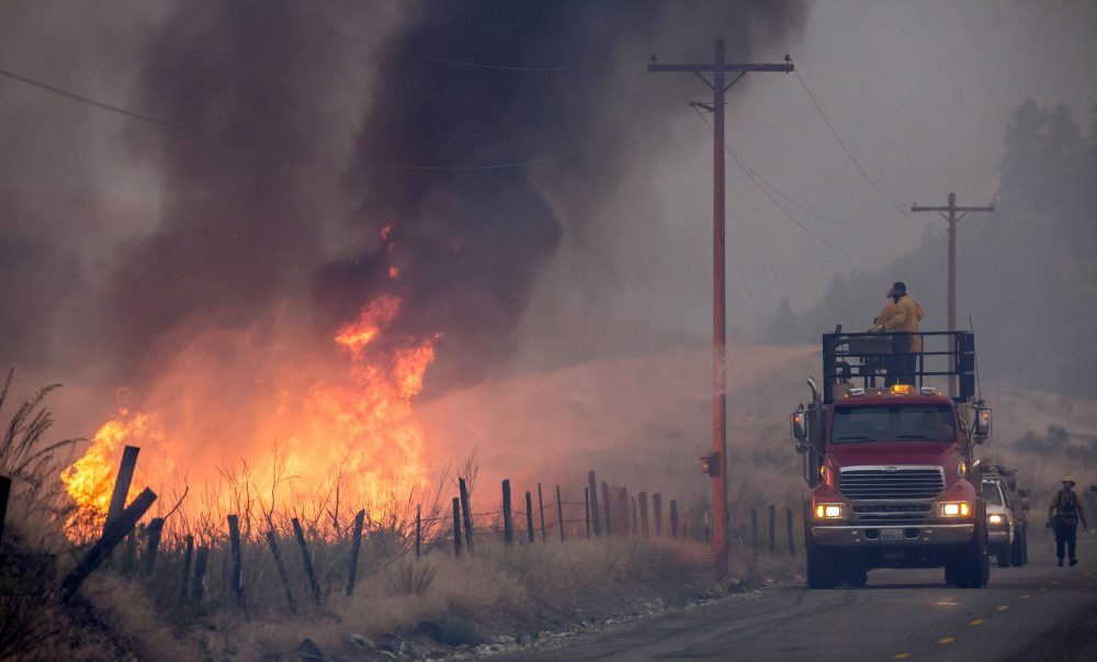 A makeshift fire truck puts water on a wildfire, which is part of the Okanogan Complex, as it burns through brush on Aug. 22, 2015 near Omak, Washington. (Stephen Brashear/Getty Images)