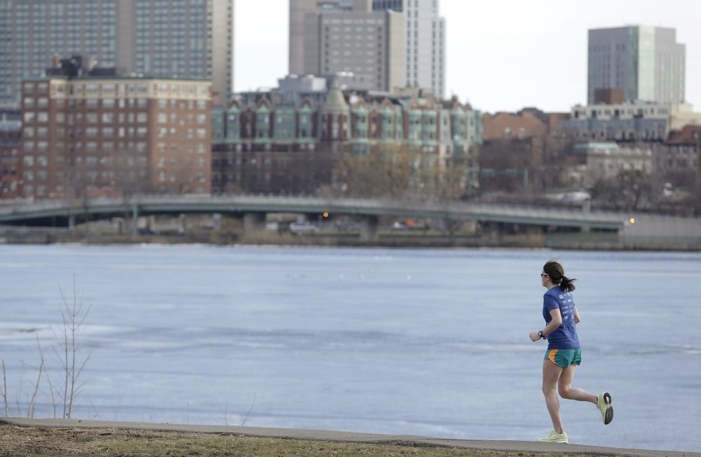 A runner makes her way along a path next to the Charles River Monday, Feb. 1, 2016, in Cambridge, Mass. (Steven Senne/AP)