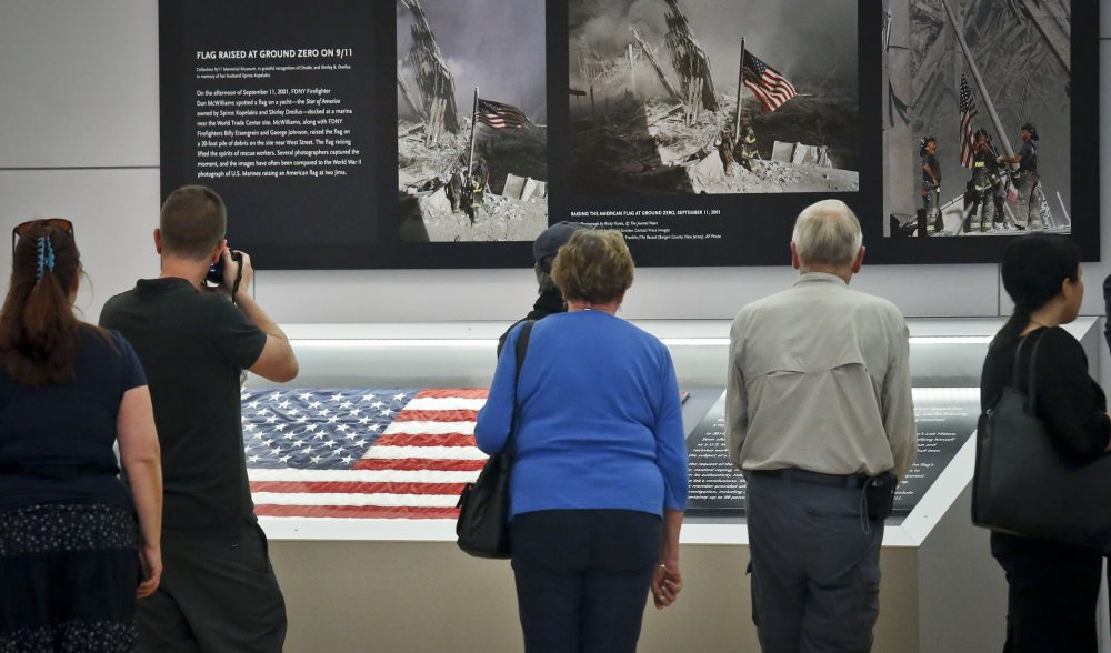 Visitors view the display for the American flag that firefighters hoisted at Ground Zero in the hours after the 9/11 terror attacks at the Sept. 11 museum in New York. (Bebeto Matthews/AP)