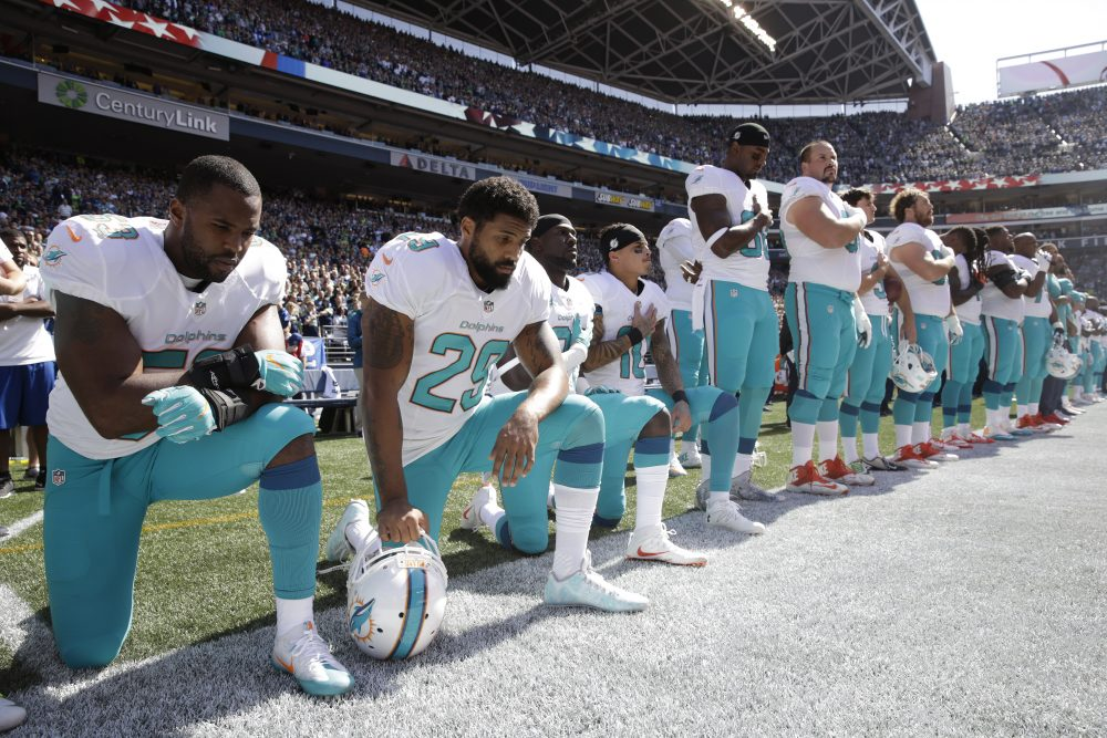 From left, Miami Dolphins' Jelani Jenkins, Arian Foster, Michael Thomas, and Kenny Stills, kneel during the singing of the national anthem before an NFL football game against the Seattle Seahawks, Sunday, Sept. 11, 2016, in Seattle. (Stephen Brashear/AP)