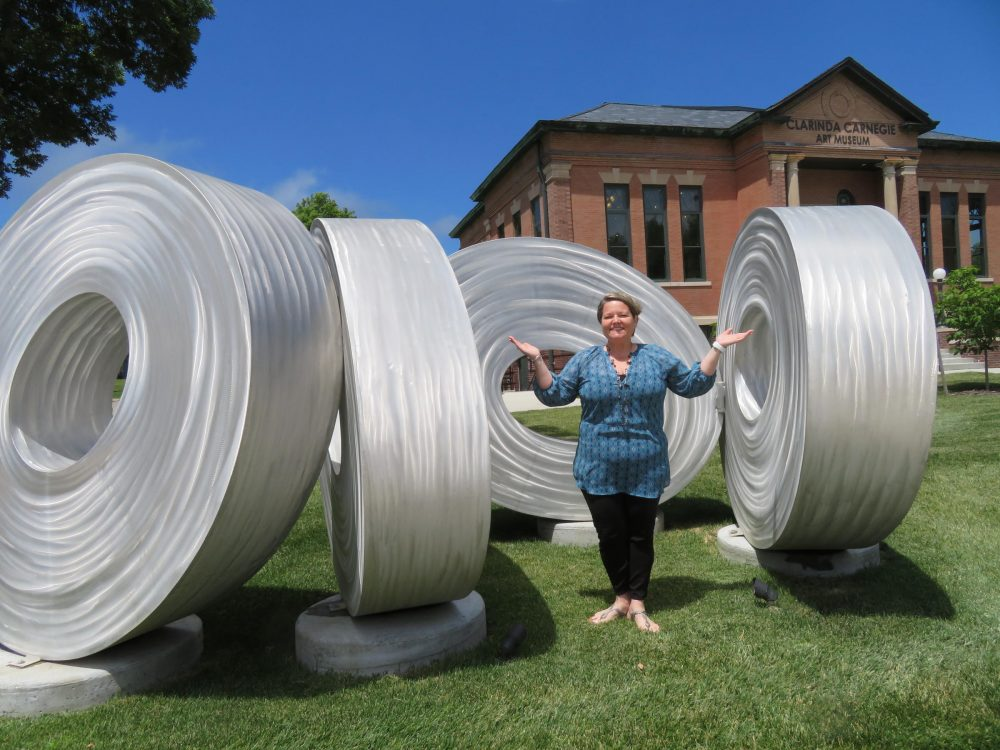 Clarinda Carnegie Art Museum Director Trish Okamoto with sculptor Brad Howe's 'Wall of Eyes' -- which one Clarinda farmer at first mistook for air-conditioning ducts. (C.J. Janovy/KCUR)