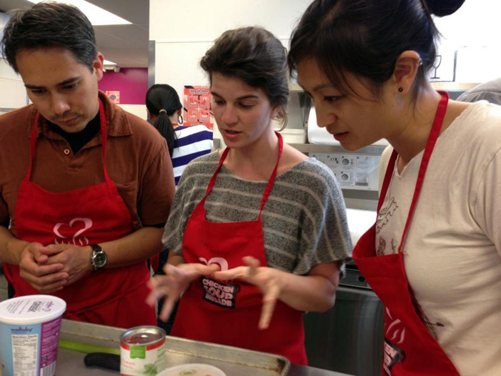 Medical residents Bryn Chowchuvech, Bari Laskow and Tiffany Ho discuss strategy for making their spaghetti dish. (Ruby de Luna/KUOW)