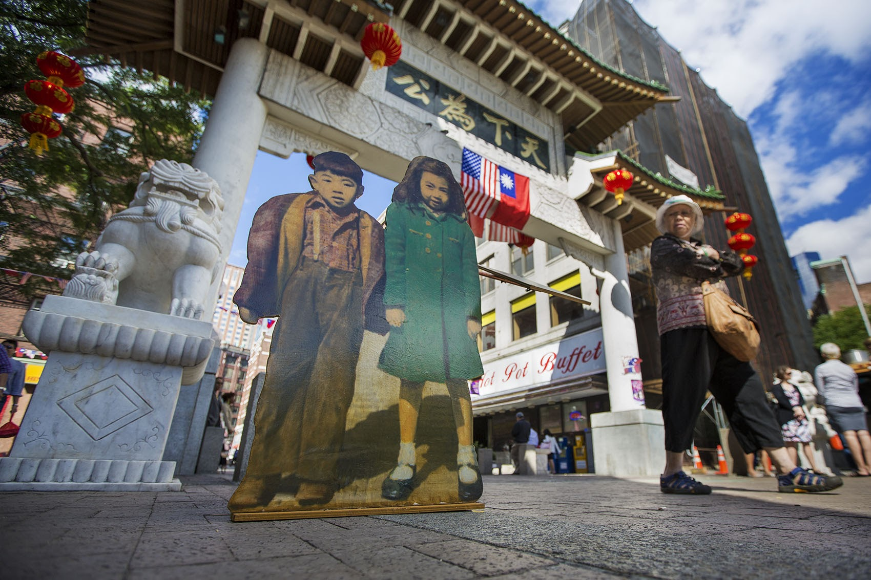 """""""Two Kids"""" stand at the Chinatown Gate as part of artist Wen-Ti Tsen's """"Home Town"""" installation. (Jesse Costa/WBUR)"""