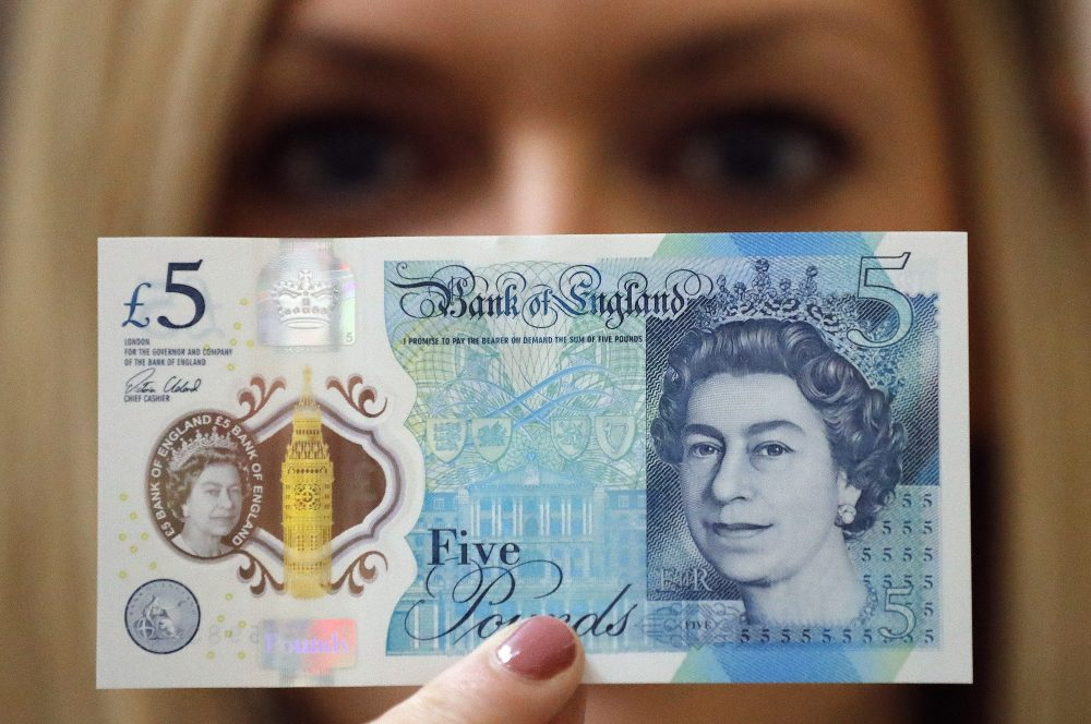 A Bank of England employee shows the new five pound note at the Bank of England Museum in London, Tuesday, Sept. 6, 2016. (Frank Augstein/AP)