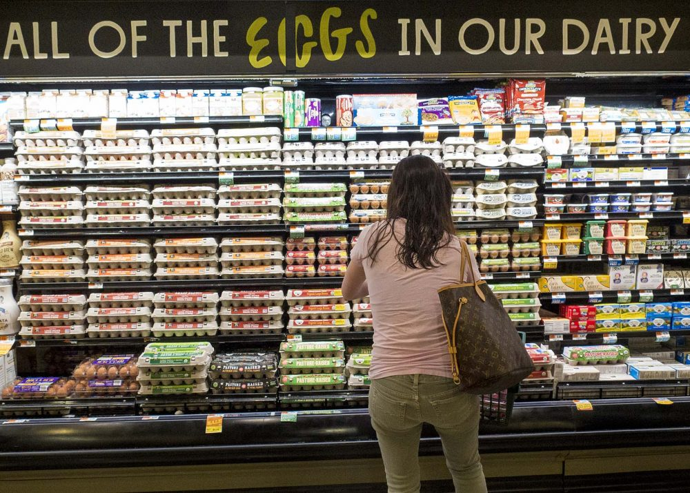 A consumer looks over Whole Foods Market's extensive selection of eggs that already comply with Question 3 requirements. (Andrea Shea/WBUR)