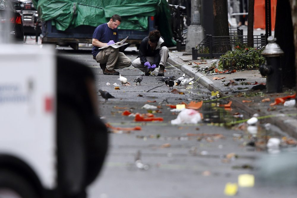Evidence teams investigate at the scene of Saturday's explosion on West 23rd Street in Manhattan's Chelsea neighborhood, Monday, Sept. 19, 2016, in New York. Ahmad Khan Rahami, wanted in the bombings that rocked Chelsea and a New Jersey shore town was captured Monday after being wounded in a gun battle with police that erupted when he was discovered sleeping in a bar doorway, authorities said. (Jason DeCrow/AP)