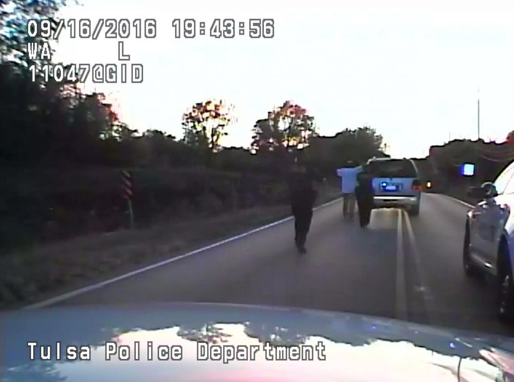 In this image made from a Friday, Sept. 16, 2016 police video, Terence Crutcher, center, is pursued by police officers as he walk to an SUV in Tulsa, Okla. Crutcher was taken to the hospital where he was pronounced dead after he was shot by the officer around 8 p.m., Friday, police said.  (Tulsa Police Department via AP)