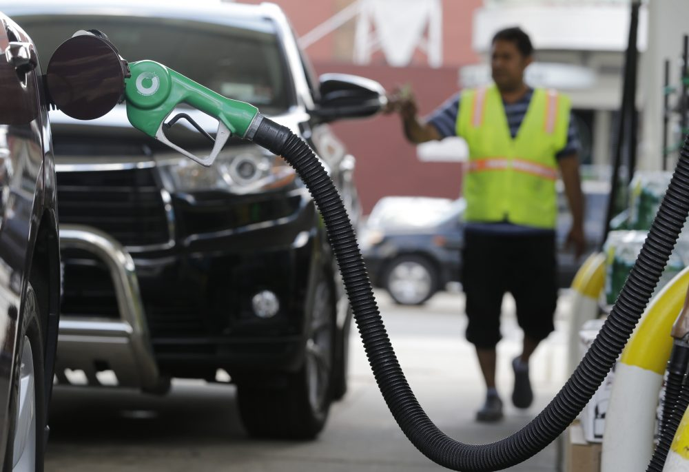 A nozzle pumps gas into a vehicle at a BP gas station. (Julio Cortez/AP)