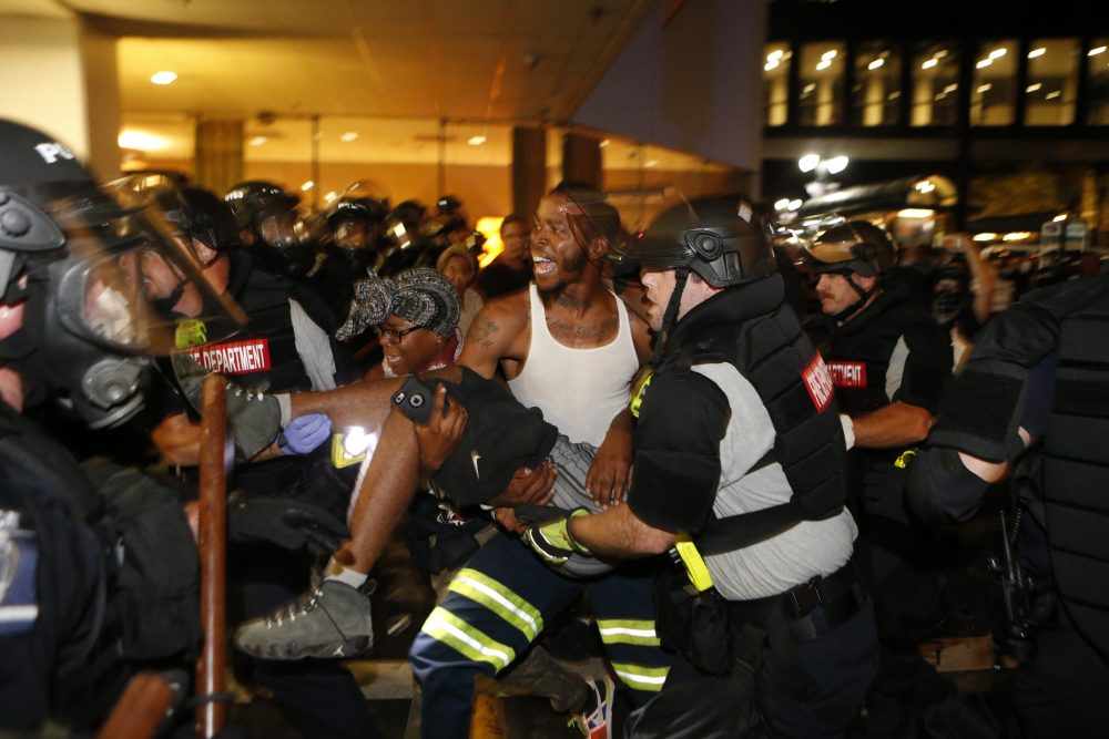 Police and protesters carry a seriously wounded protester into the parking area of the the Omni Hotel during a march to protest the death of Keith Scott Sept. 21, 2016 in Charlotte, N.C. (Brian Blanco/Getty Images)