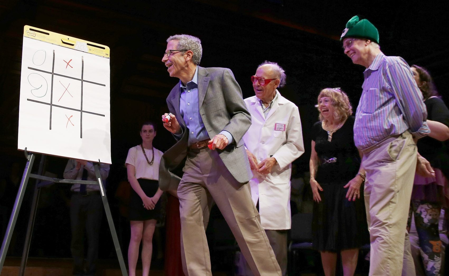 """Nobel laureates Rich Roberts (physiology or medicine, 1993), right, Dudley Herschbach (chemistry, 1986) third from right, and Eric Maskin (economics, 2007), second from left, compete in a game of """"tic-toc-toe"""" with a brain surgeon during the Ig Nobel award ceremonies. (Michael Dwyer/AP)"""