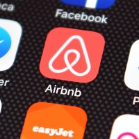 The Airbnb app logo displayed on an iPhone. (Carl Court/Getty Images)